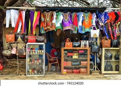 Street market in Ghana. Woman sales clothes in traditional Ghanaian style, bags, shoes, accessories. Business in developing countries. Modern national clothing. Fashion. Ghana, Accra -January 20, 2017