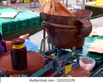 street market with vintage blue enamel finished weighing scale. rusty galvanized bucket. selective focus on scale. blurry background. fruit and vegetable market before closing. empty display tables.
