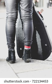 Street musician artist in skinny black trousers and black stylish chelsea boots stands on walk path with guitar in guitar case cover. Shot from back focus on red sock, crop in half legs