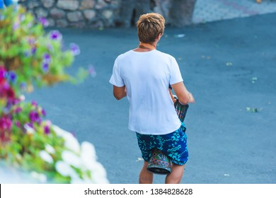 Street musician. Guy holds in hands of the ethnic drum. Pink and purple flowers growing on the fence. Musical instrument drum darbuka.