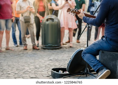 Street musician playing guitar on city street in summer