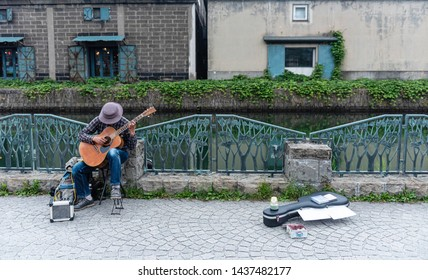 Street musician playing guitar on street with old building background