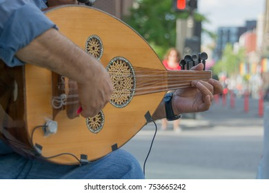 Street musician playing an oud busking for money
