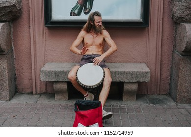 A street musician plays the drum. Charismatic hippies in the center of the city. The drummer plays African motifs