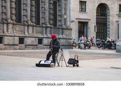 street musician in the red hat playing the saxophone in Milan Italy