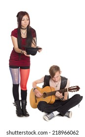 Street musicians play and sing on guitar. Asian woman and Caucasian man.