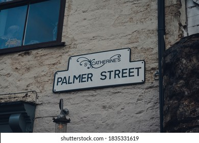 Street name sign on a brick wall of a building on Palmer Street in St Catherines Artisan Quarter in Frome, Somerset, UK.
