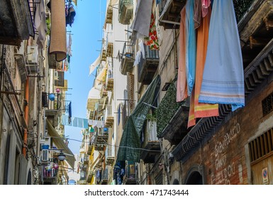 Street of Naples, June 13, 2016 in Naples, Italy. Architectural details with old buildings across street and things hanging from balconies.