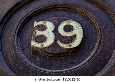 Street number. Number 39. Numbers of gilded metal on round of blue wood.