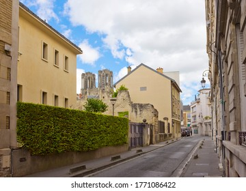 Street with old houses and tower of Reims Cathedral in Reims, France