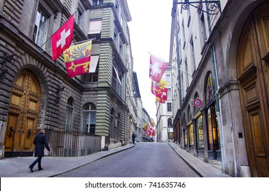 A street in Old Town Geneva with Swiss Flag and Geneva Flag on the 2 sides of the road.
