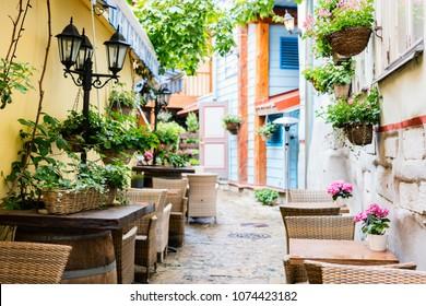 Street with outdoor restaurant tables in Tallinn old town, Estonia, Europe