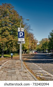 Street with paid parking spots with trees and colorful leaves in the autumn season on October 2017 in Poznan, Poland