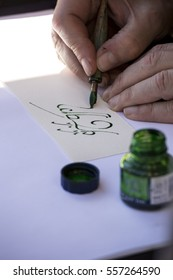 street painter writing a celtic name with green pen .