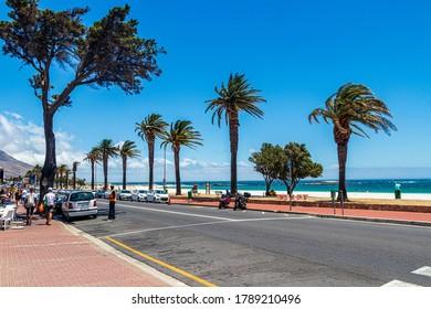 Straße mit Palmen und Strand in Camps Bay, Kapstadt.