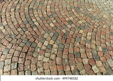 Street paved with cobblestone. Urban stone paving stones. Stone road texture. Ancient cobblestone road. Abstract background of old cobblestone pavement. Paris, France