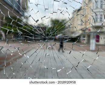 A street with a pedestrian seen through a broken window. Probably a case of vandalism.