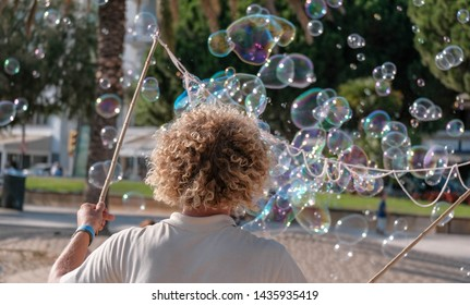Street performer blowing soap bubbles outdoor. Young man entertains tourists on the street in summer. Funny caucasian man with blond curly hair makes big colorful soap bubbles.