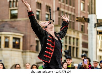 A street performer doing a show in Dam Square, Amsterdam, the Netherlands, holds his hands up in victory after successfully swallowing a sword in front of a crowd.