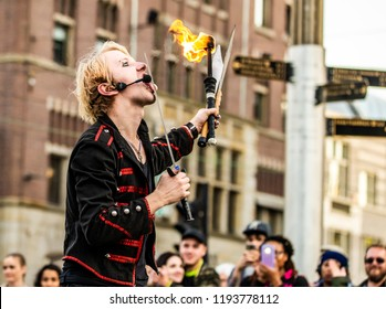 A street performer doing a show in Dam Square, Amsterdam, the Netherlands, licks a sword before swallowing it in his performance. He also holds a lit fire stick and two large knives.