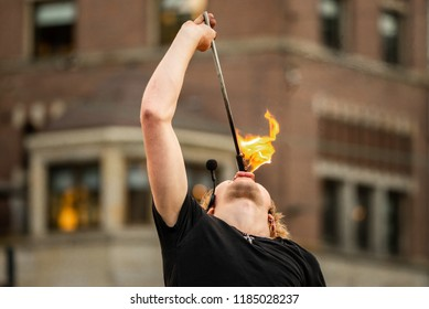A street performer performs a fire manipulation stunt in his show in Dam Square, Amsterdam, by putting a lit fire stick in his mouth to extinguish the flame.
