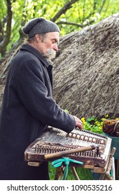 Street performer plays cimbalom special string wooden musical instrument. Folk musician play in pirogovo. Medieval minstrel playing tambal, hammered dulcimer with hammers. May 02, 2016 Kiev, Ukraine.