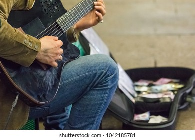 Street performer plays guitar at night  - shallow focus with blur background of his guitar case full with banknotes and coins