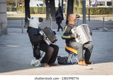 Street performers play on accordion in horse masks. Outdoor show. Vienna, Austria.