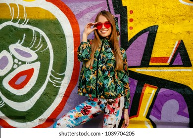 Street photo of beautiful girl in red eyeglasses. Dressed up in green colorful jacket, and pants. Standing on the background with graffiti.