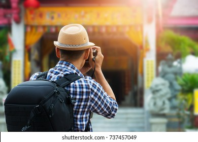 Street photographer taking a picture of old shrine chinese temple in phuket old town ,rear view. Tourist sightseeing old town, travel concept.