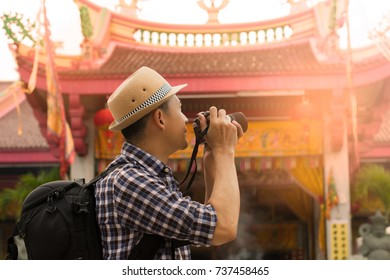 Street photographer taking a picture of old shrine chinese temple in phuket old town with vintage camera ,side view. Tourist sightseeing old town, travel concept.