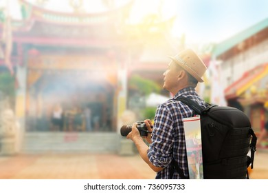 Street photographer wandering to old shrine chinese temple in phuket old town,side view.