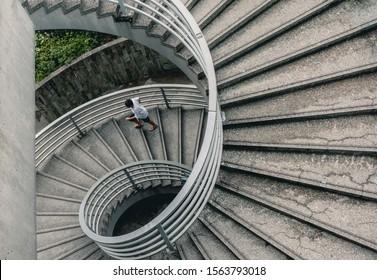 Street Photography of Man Walking Down Spiral Stairs in Hong Kong