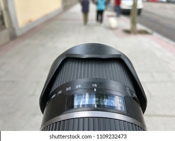 street photography. subjective view of the photographer taking pictures in the street. first person view on a camera lens or photographic objective.