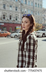 Street portrait of a beautiful brunette woman in a plaid shirt. Sunglasses on the head. Reflection of the sky in glasses glasses. Inviting look of a young woman. Mysterious smile.