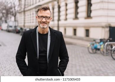 Street portrait of cheerful mature man wearing black coat