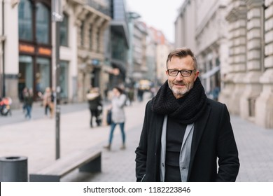 Street portrait of cheerful mature man wearing black coat