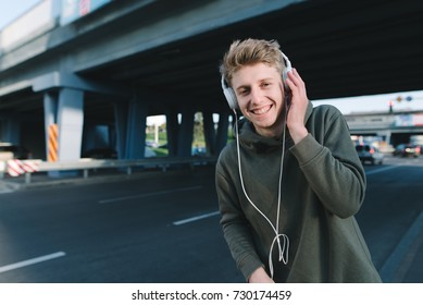 Street portrait of a happy student in headphones on the head of a city background. A funny young man walks around the city.