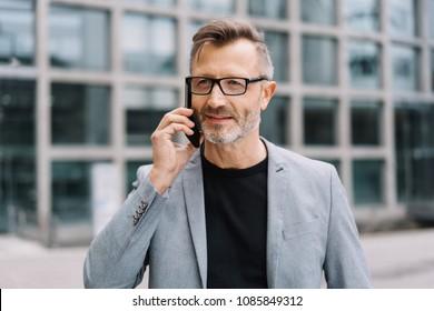 Street portrait of mature bearded man wearing grey jacket talking on mobile phone