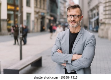 Street portrait of mature man with arms crossed wearing grey jacket