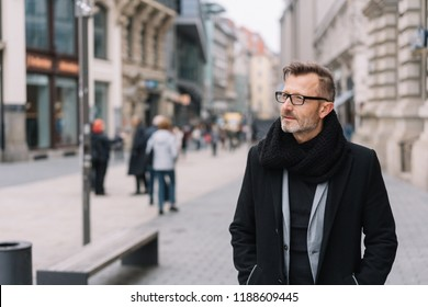 Street portrait of mature man with glasses wearing black coat