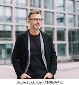 Street portrait of mature man with glasses wearing black coat