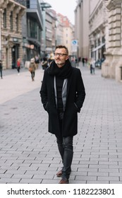 Street portrait of mature man wearing black coat