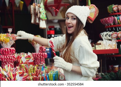 Street portrait of smiling beautiful young woman buying candy on the festive Christmas fair. Lady wearing classic stylish winter knitted clothes. Close up
