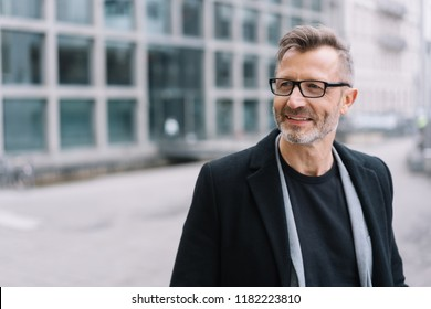 Street portrait of smiling mature bearded man with glasses wearing black coat