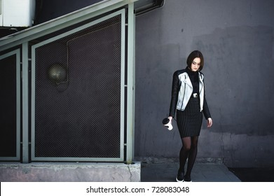 street portrait of a student girl dressed fashionably in dark clothes, on an autumn sunny day