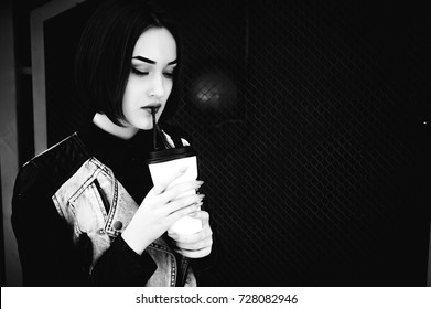 street portrait of a student girl, fashionably dressed in dark clothes, with a black backpack and a denim jacket, with a corton cup of a hot coffee drink Takeaway on an autumn sunny afternoon