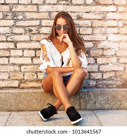 Street portrait of stylish girl in jeans shorts and sunglasses