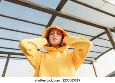 Street portrait of a stylish girl in a yellow hoodie, looking into the camera and posing. Hood on the head. Fashionable girl in street clothes poses