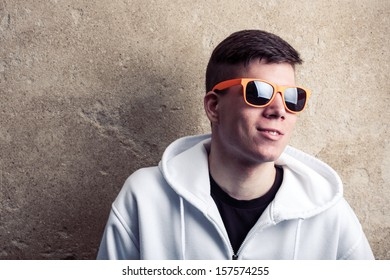 Street portrait of young boy in white sweatshirt with orange modern eyeglasses near old wall, street atmosphere, landscape, young generation, street life